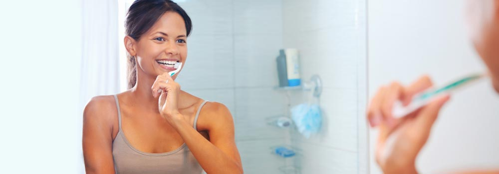 Young woman shows How To Brush Your Teeth