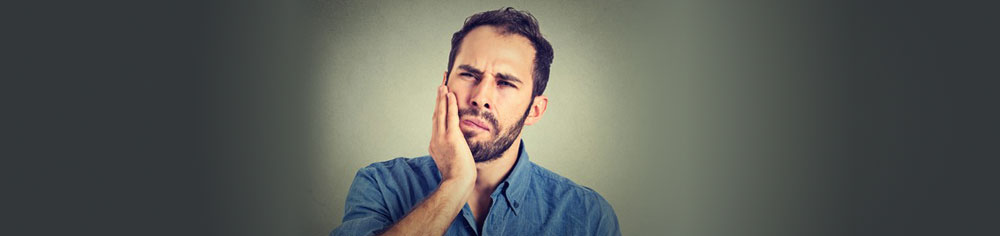 Problems caused by Wisdom Teeth - a young man in pain